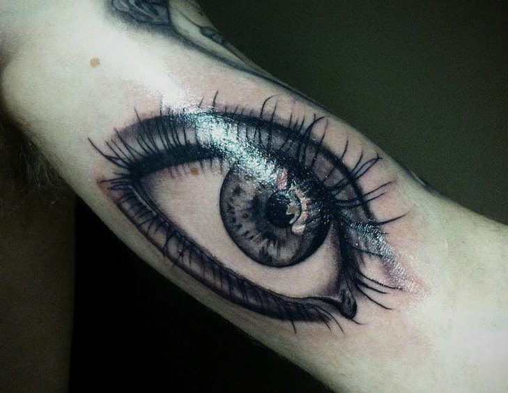 eye tattoo realism, black and grey by award winning artist, real eye tattoo on upper arm, large inner arm tattoo